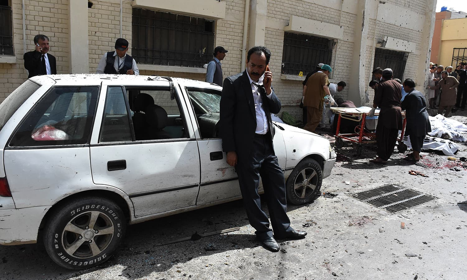 Lawyers talk on mobiles next to bodies of their colleagues after a bomb explosion at a government hospital premises in Quetta on August 8, 2016.—AFP