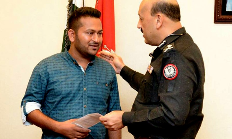 "Sindh Inspector General (IG) AD Khawaja awarding a Rs50,000 prize to citizen Yasir Jamil for his ""valiant"" efforts against alleged robbers. —Photo courtesy Sindh police"