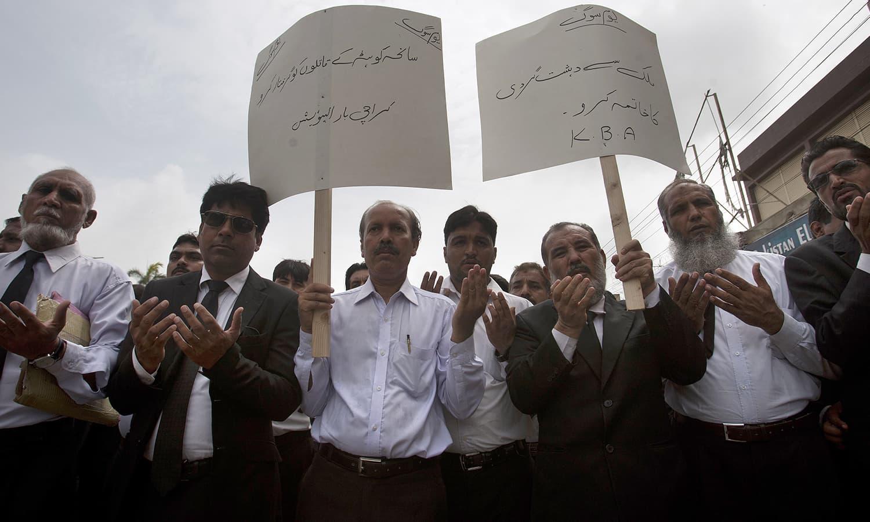 احتجاجی مظاہروں اور ریلیوں میں وکلاء دہشت گردی کے خلاف ہاتھوں میں بینرز لیے نظر آئے — فوٹو/ اے پی