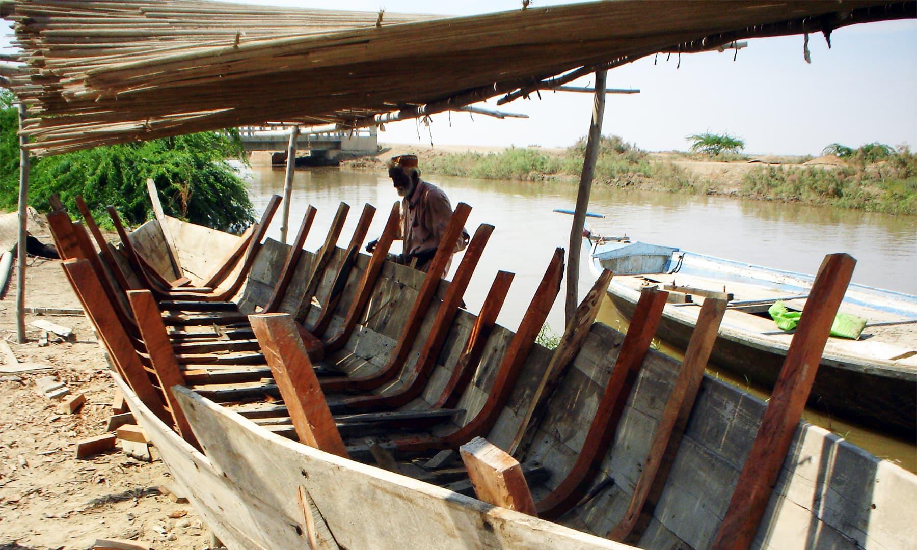 ایک ماہی گیر اپنی کشتی بنانے میں مصروف ہے — ابوبکر شیخ