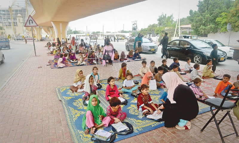 The open-air classes of the Footpath School under the Bahria Icon Tower flyover. —Fahim Siddiqi/White Star