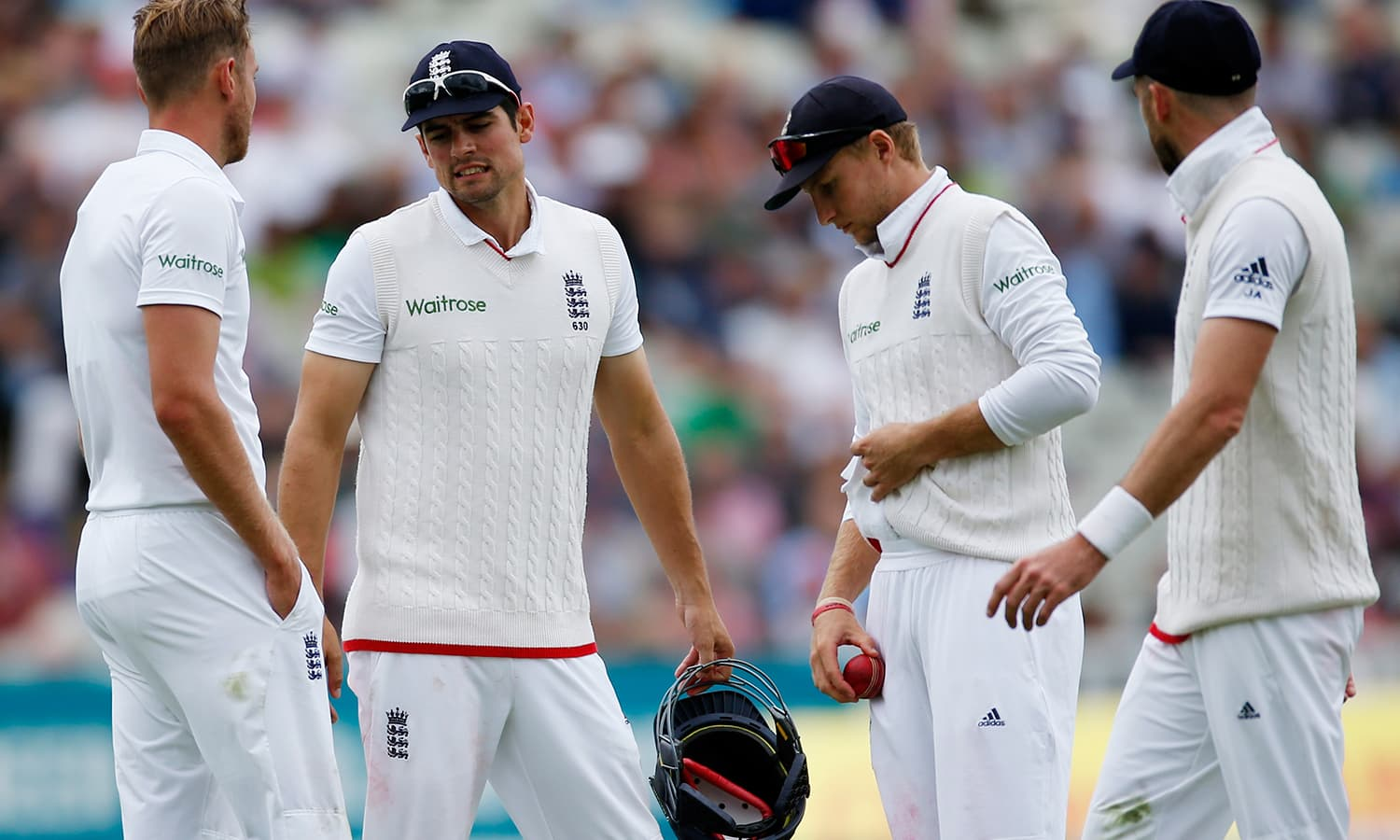 England's Joe Root shines the cricket ball (2nd R) as Stuart Broad and Alastair Cook look on during the match. — Reuters