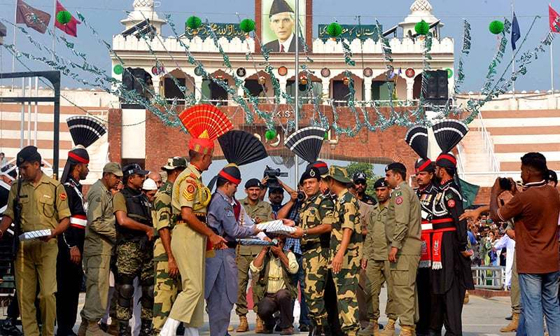 Rangers Sector Commander Shaukat Ali presents sweets to BSFCommandant Sudeep during a ceremony at Wagah. ─AFP