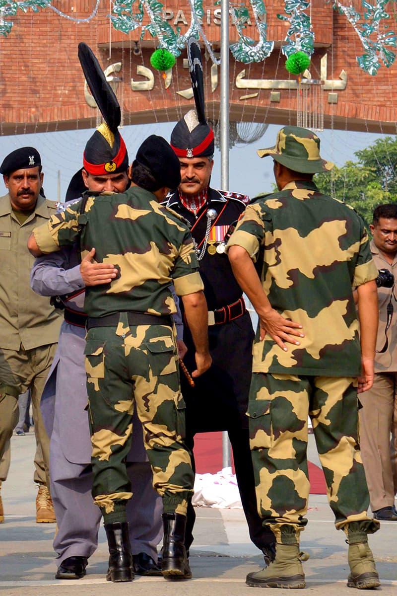 Rangers Sector Commander Shaukat Ali hugs BSF Commandant Sudeep before presenting sweets. ─AFP