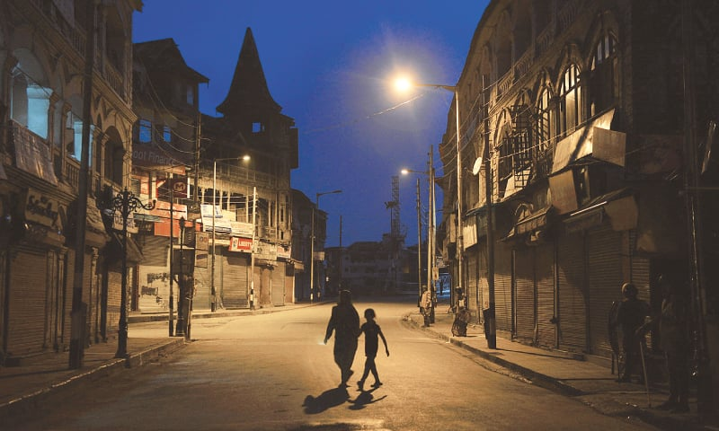 SRINAGAR: A woman and a child cross a street in the Lal Chowk area during a curfew on Sunday. Security has been beefed up across India-held Kashmir ahead of India's Independence Day on Monday.— AFP