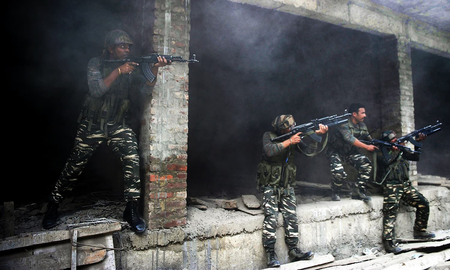 Indian army troops take position inside a building after a gunfight in Srinagar on August 15, 2016. — AFP