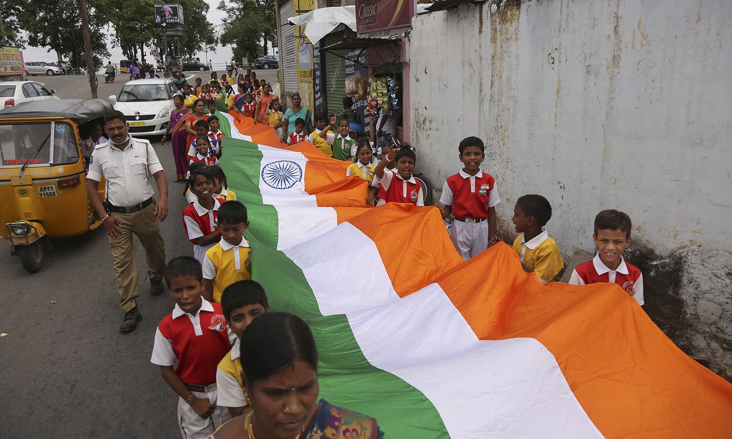 Indian school children carry a long national flag through a street during Independence Day celebrations in Hyderabad, India, Monday, Aug. 15, 2016. ─ AP