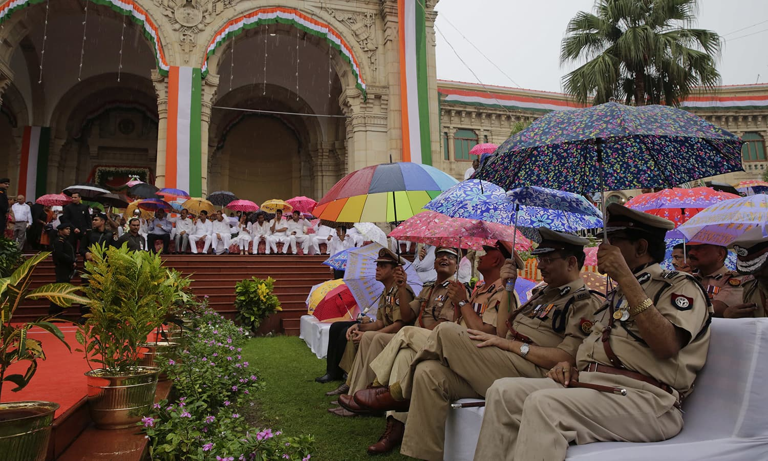 Uttar Pradesh state officers hold umbrellas as it rains during the national flag hoisting ceremony on Independence Day in Lucknow, India, Monday, Aug. 15, 2016. ─ AP