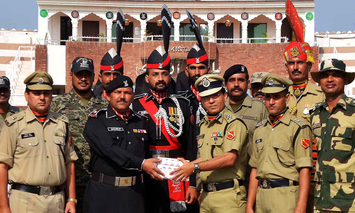 Indian Border Security Force (BSF) Commandant Sudeep (5R) presents sweets to Pakistani Superintendent of Rangers Ashraf (3L) during a ceremony to celebrate India's Independence Day at the India-Pakistan Wagah border post on August 15, 2016. ─ AFP
