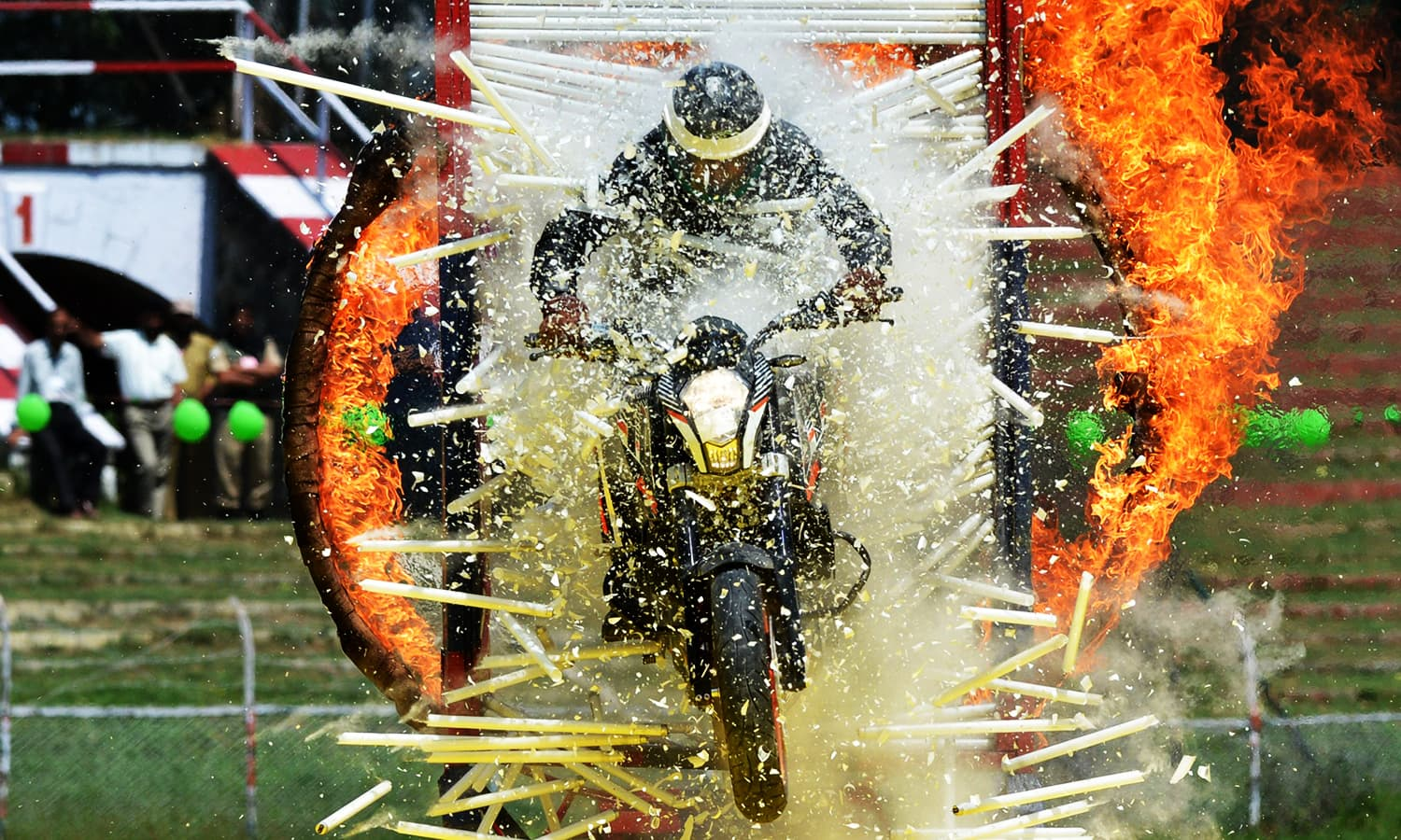 A police motorcyclist rides through a burning hoop and a wall of glass tubes during an Independence Day event at The Bakshi Stadium in Srinagar on August 15, 2016. ─ AFP