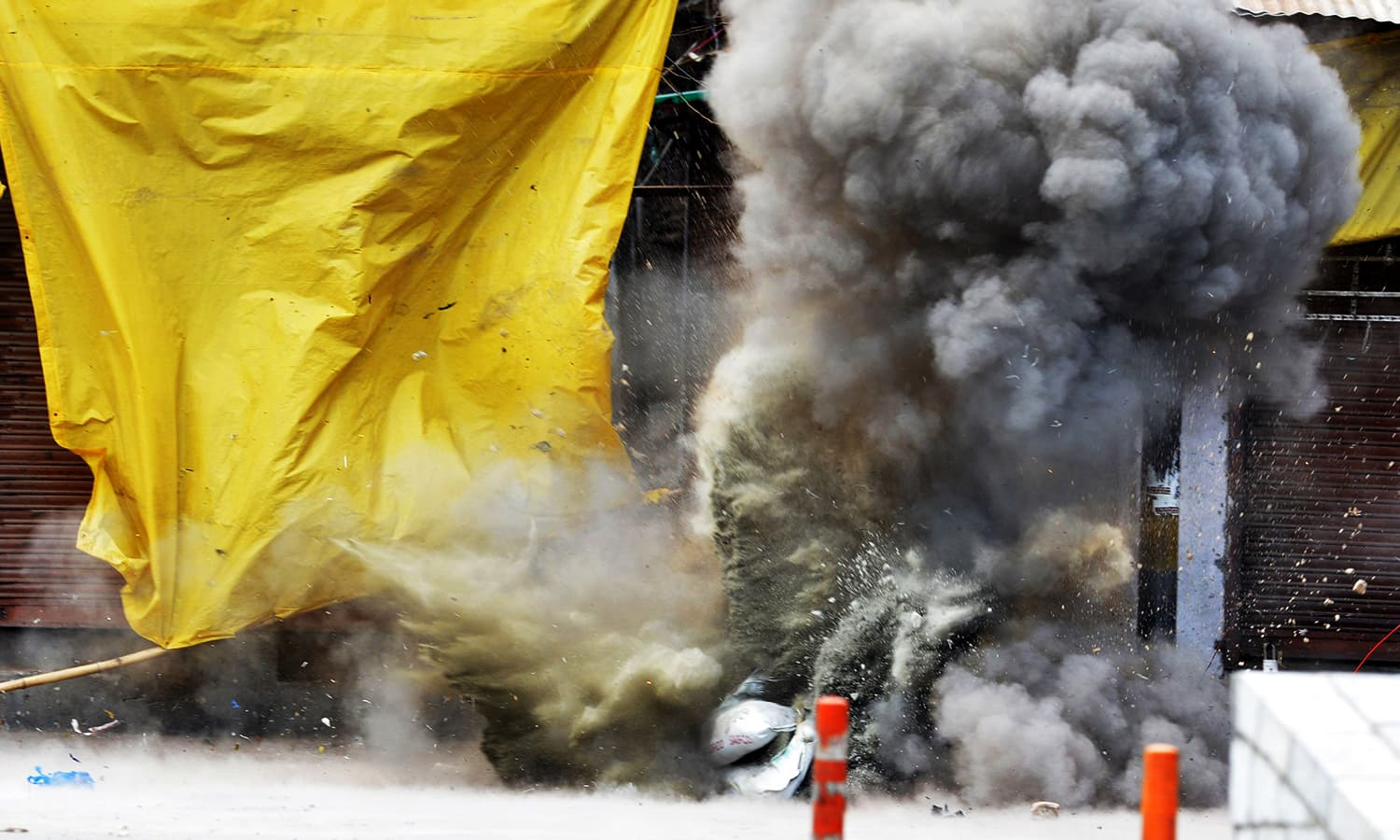 Smoke rises as unseen members of a Bomb Disposal Squad (BDS) conduct a controlled explosion of a handgrenade after a gunfight in Srinagar on August 15, 2016. ─ AFP