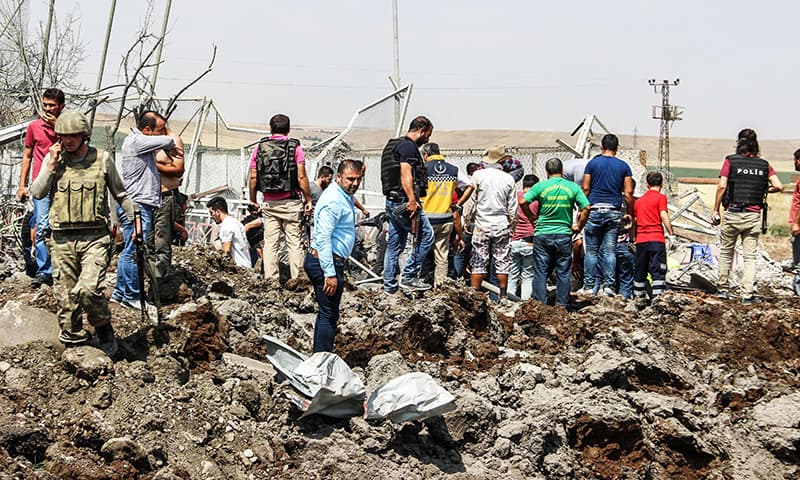 Turkish police officers and rescue personnel search the site of a car bomb explosion. -AFP