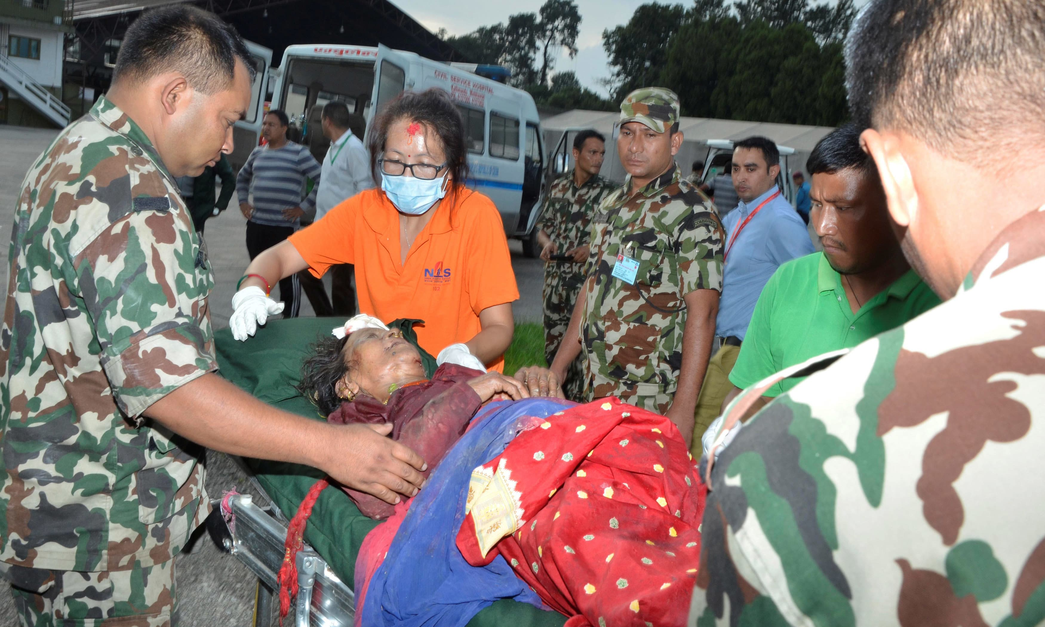 Army personnel assist a victim of a bus accident after being airlifted from Birtadeurali in Kavre to Kathmandu. —Reuters