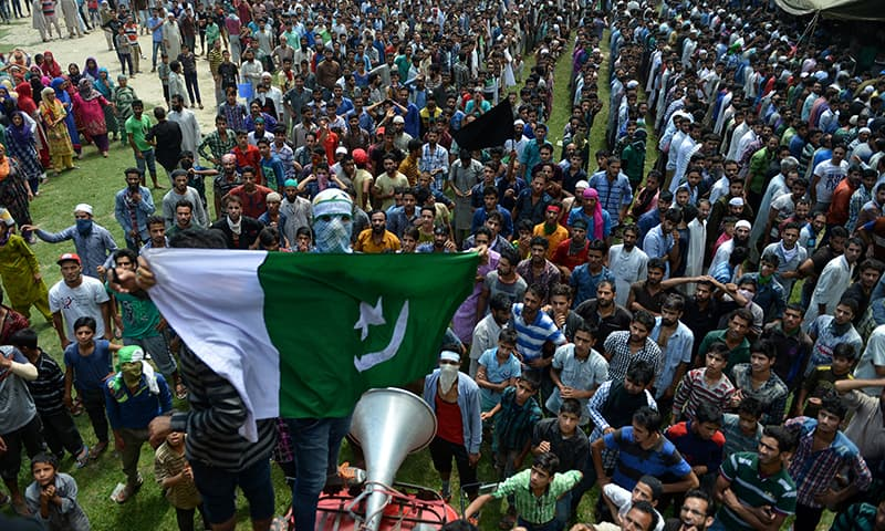 A masked Kashmiri mourner holds up a Pakistani flag as others shout anti-Indian and pro-freedom slogans during the funeral of four civilians in Aripanthan village, on the outskirts of Srinagar on August 16, 2016.  — AFP