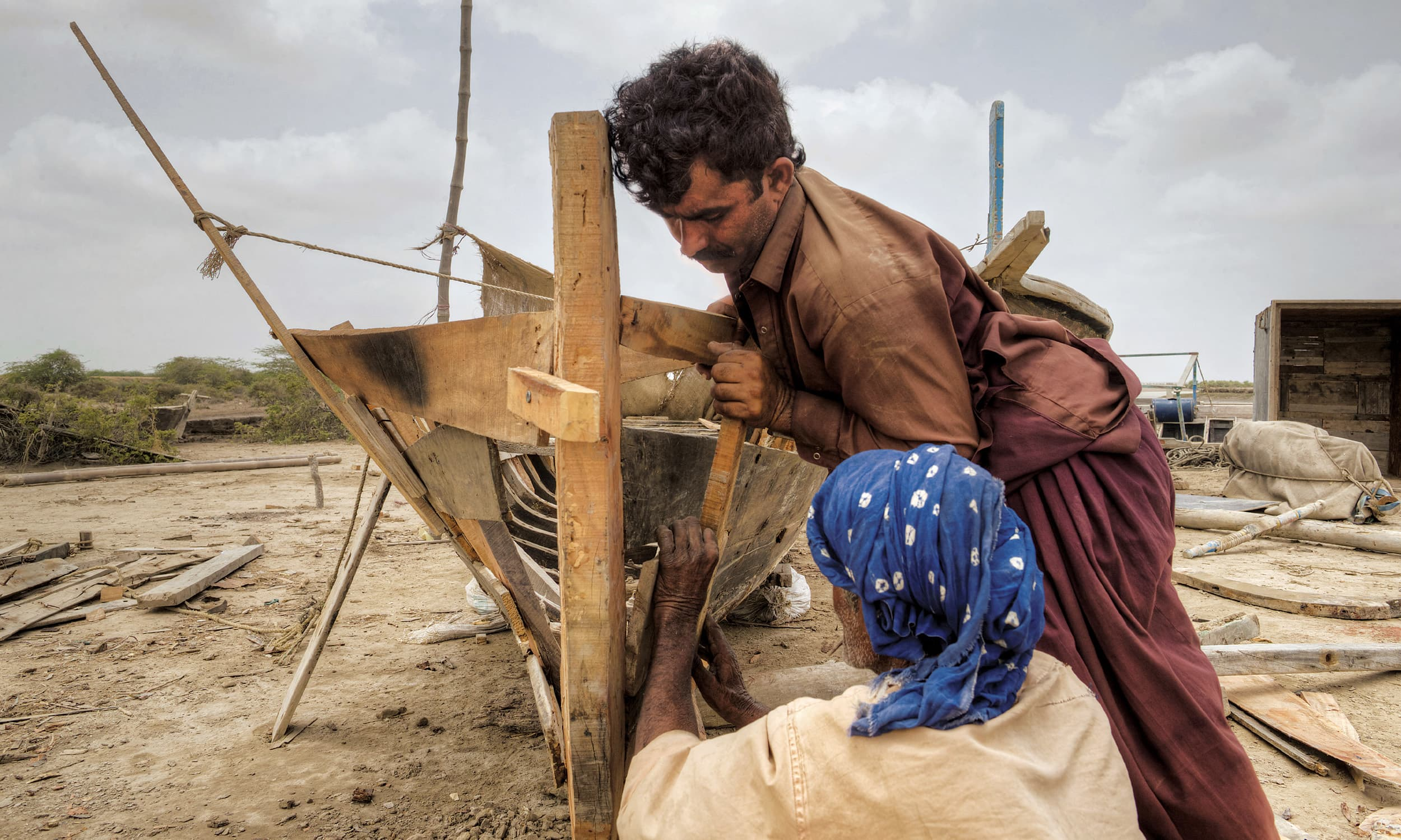 A carpenter and his apprentice at work on a boat close to the Pakistan-India border near Shah Bandar | Kohi Marri