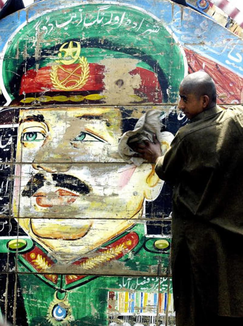A driver wipes off dust from the portrait of Ayub Khan which was originally painted on this truck in 1966.