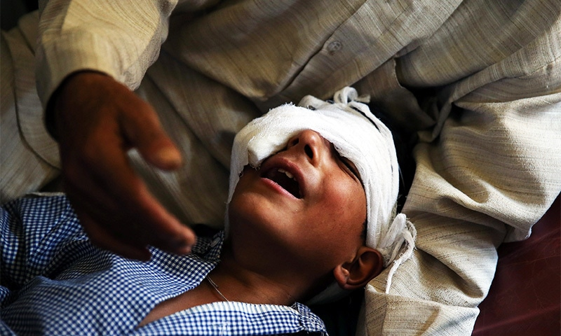 A father comforts his son whom he said was injured by pellets shot by security forces in Srinagar following weeks of violence in Kashmir, August 18.—Reuters