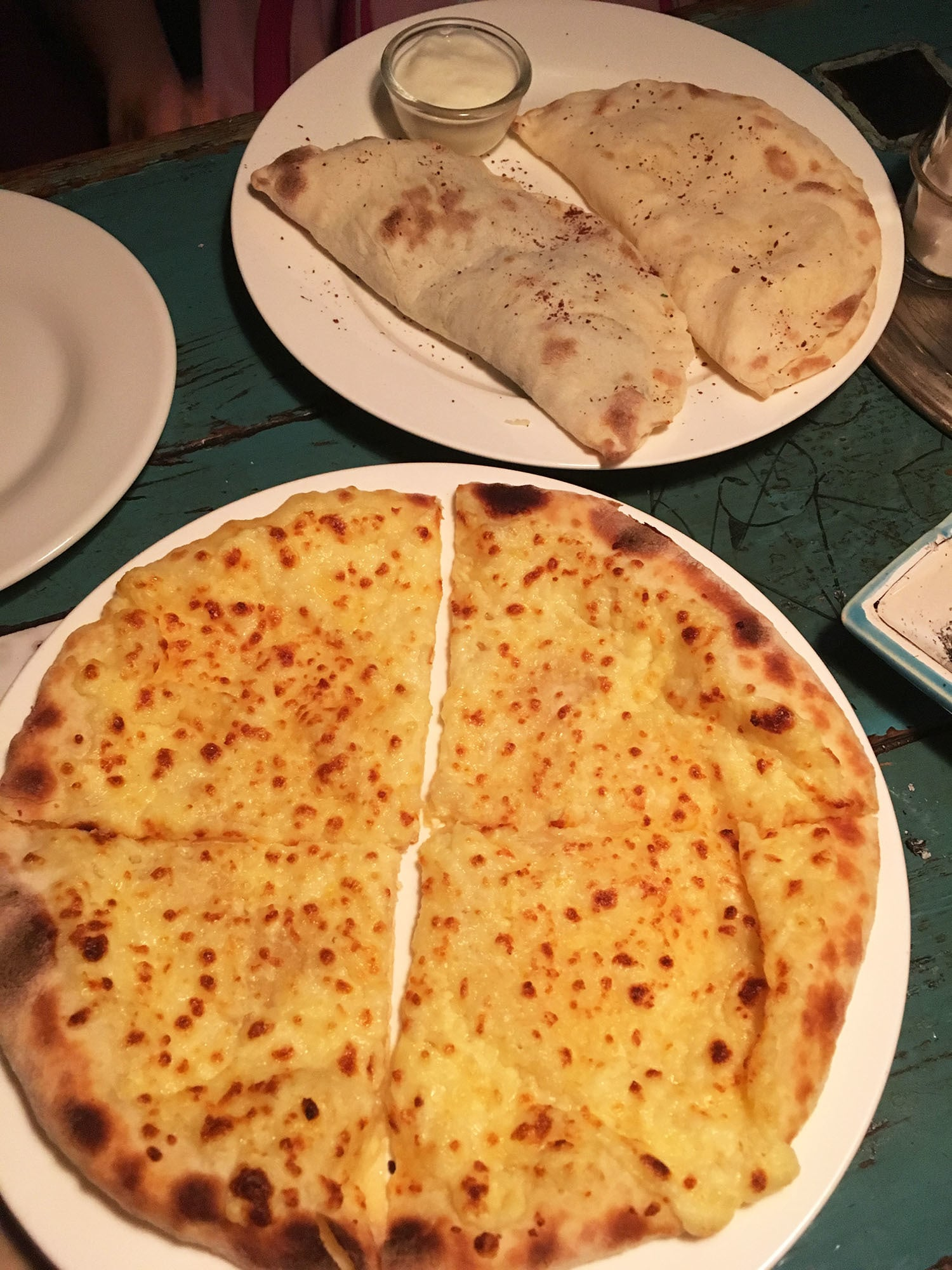 Having cheese-filled khachapuri bread.