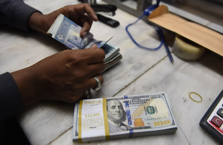 A currency dealer counts rupees and dollars at a currency exchange.—AFP file photo