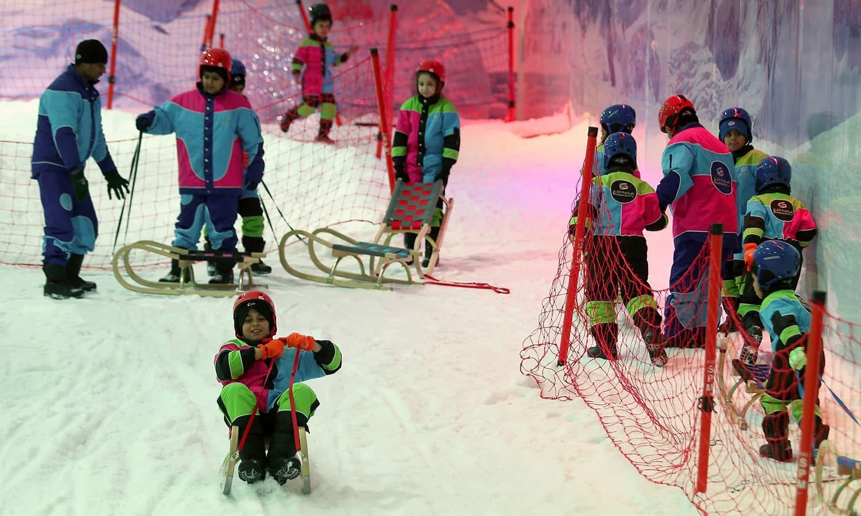 اسنو ۔سٹی تھیم پارک میں داخل ہوتے ہی شہریوں کو مخصوص لباس اور جوتے فراہم کیے جاتے ہیں تاکہ وہ کم درجہ حرارت کا مقابلہ کر سکیں — فوٹو/ ای ایف پی