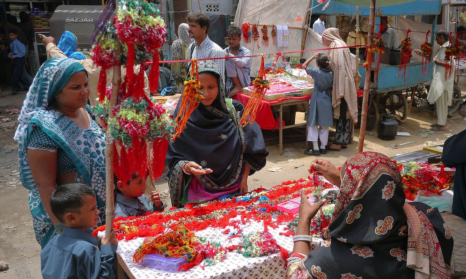 رکشا بندھن کے موقعے پر بہنیں اپنے بھائیوں کے لیے راکھی خرید رہی ہیں