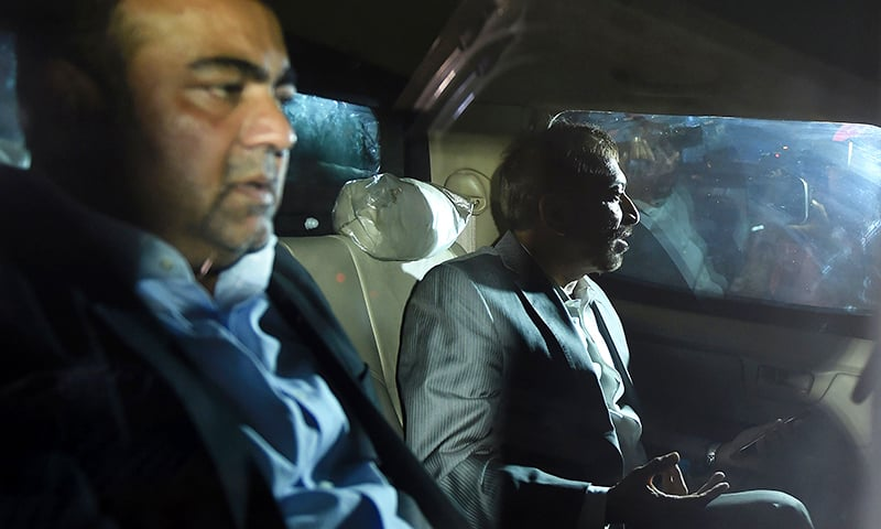 Farooq Sattar and Khawaja Izhar sit in a car as they leave after being taken into custody. —AFP