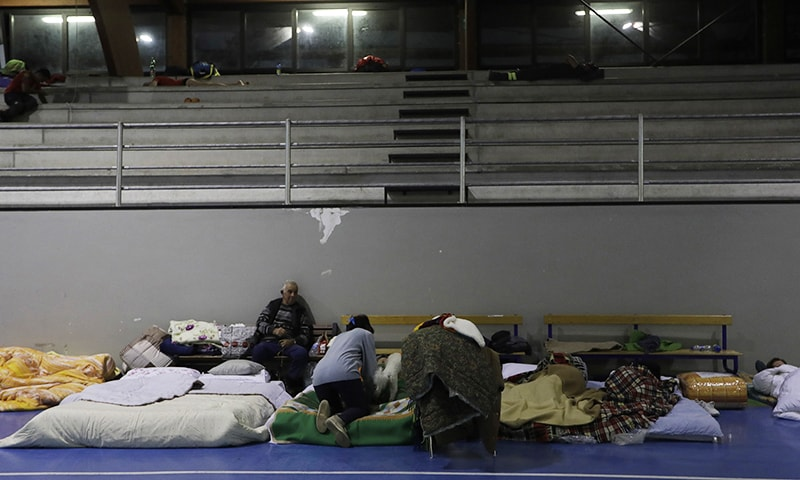People prepare to spend the night in a gymnasium. Residents have been advised not to return to their homes. ─AP