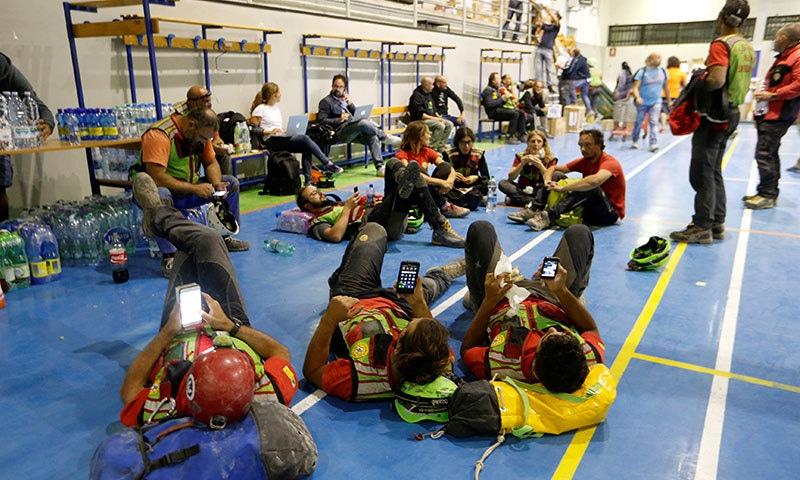 مسلسل امدادی سرگرمیوں میں مصروف رہنے کے بعد ریسکیو اہلکار بھی آرام کررہے ہیں—فوٹو/ رائٹرز