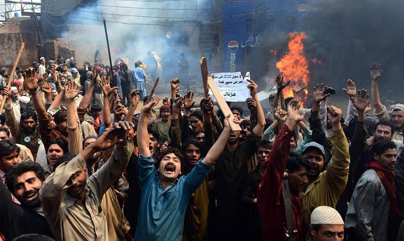 An angry mob of Muslim men shout slogans in a Christian neighbourhood in Lahore, Pakistan | AFP