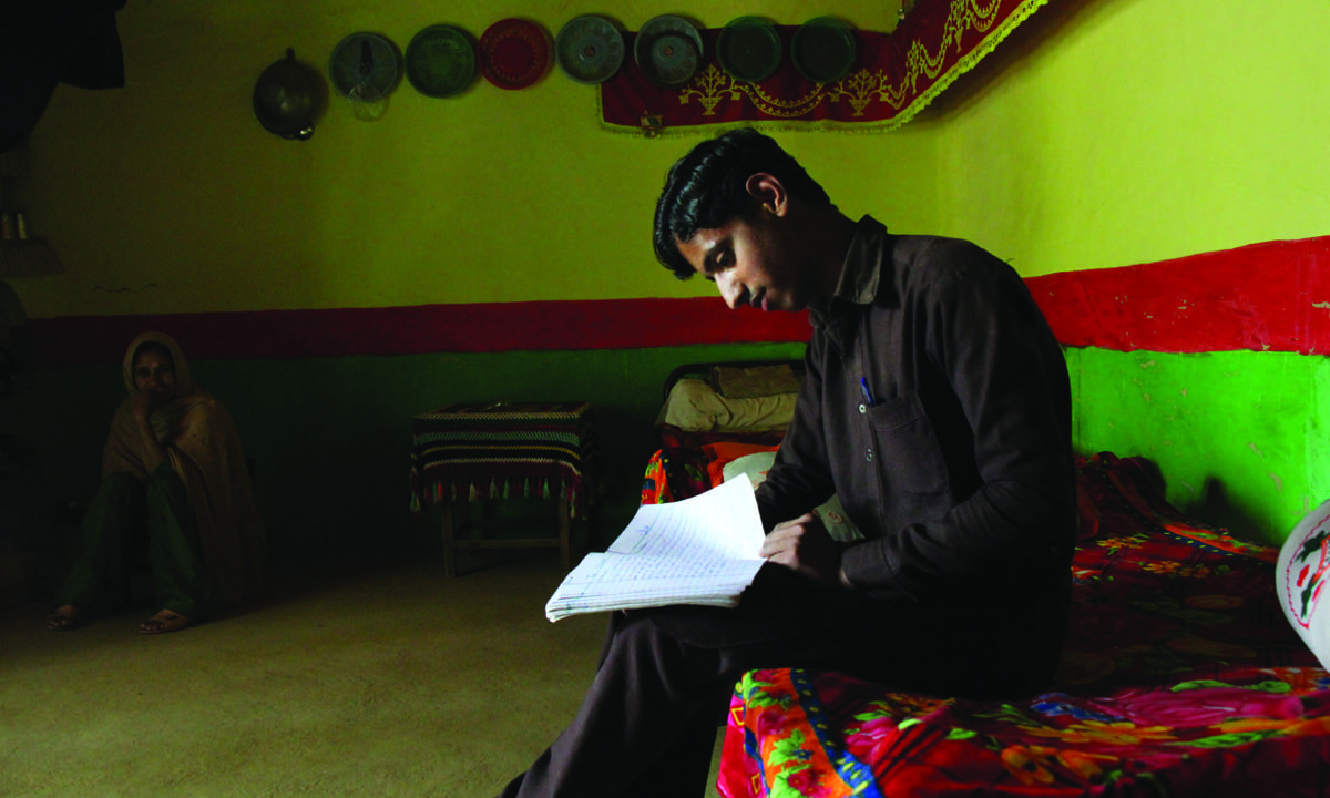 Ambreen's brother Nauman looks through his notebook  at his house in Makol |  Annie Ali Khan