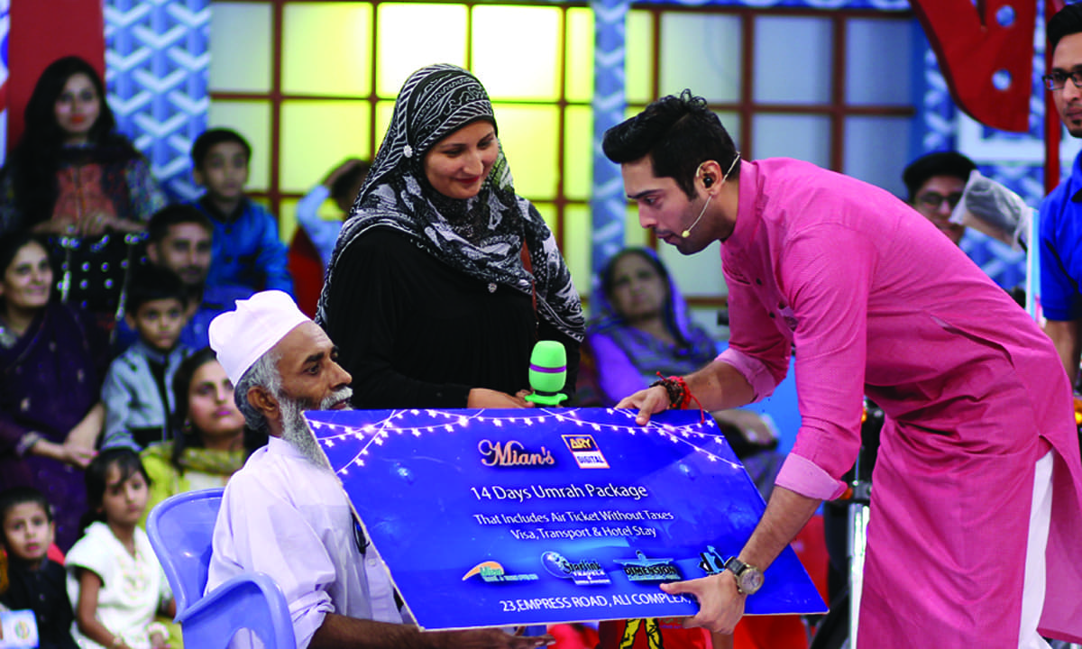 Fahad Mustafa hands out an umrah package to an audience member | Courtesy ARY Digital