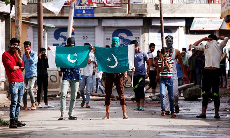 Protesters hold the flag of Pakistan during a protest in Srinagar against the recent killings in Kashmir. -Reuters