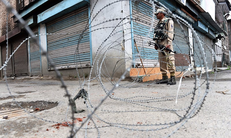 An Indian paramilitary trooper stands guard during curfew in downtown Srinagar. —AFP