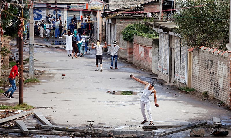A protester hurls a stone towards the Indian police during a protest in Srinagar against the recent killings in Kashmir. -Reuters