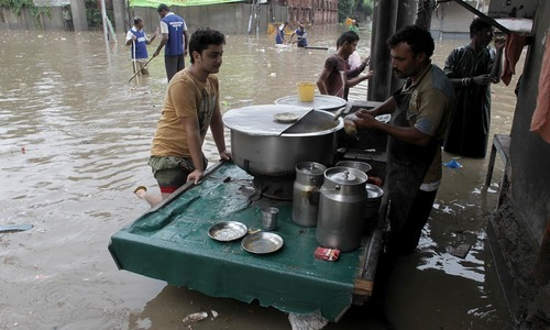 Some people kept enjoying the weather and visited food stalls during the rain. — AFP
