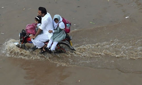 Parents faced inconvenience due to rain water on roads to drop their children to school.  —AFP