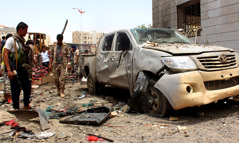 Yemenis, including soldiers, inspect debris at the site of a suicide car bombing claimed by IS on August 29, 2016 at an army recruitment centre in Aden. ─AFP