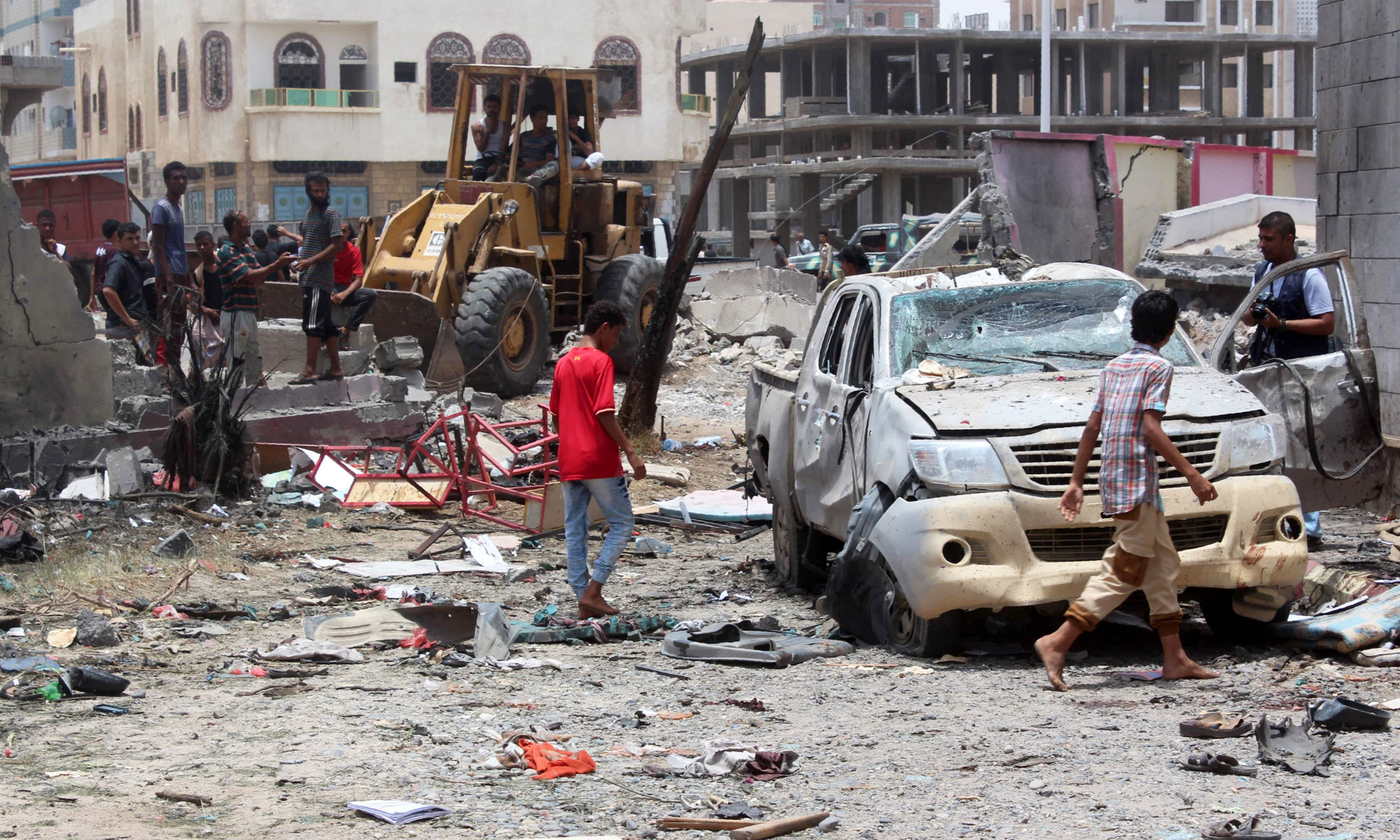 Yemenis inspect the site of a suicide car bombing claimed by the Islamic State. —AFP