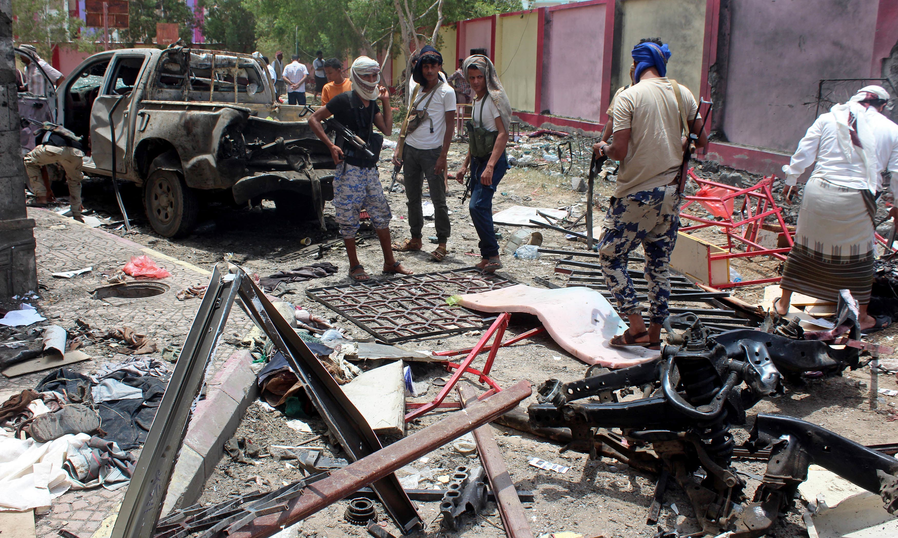 Fighters loyal to the government gather at the site of a suicide car bombing in Yemen. —AP