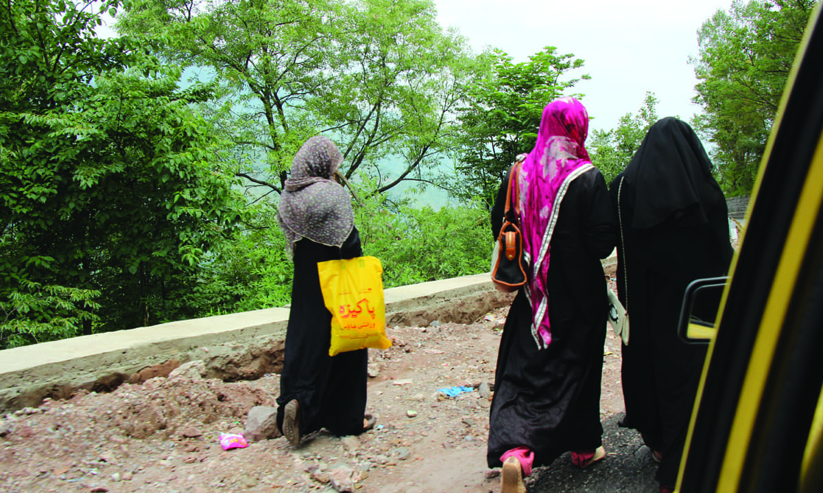 Women clad in burqas walk along a road near Dewal Sharif | Annie Ali Khan