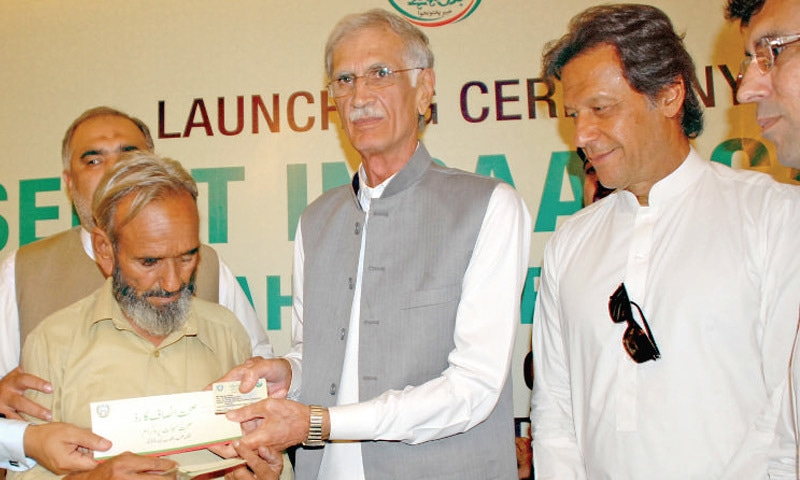 Chief Minister Pervez Khattak gives away Sehat Insaf Card to a man as Imran Khan looks on at a ceremony in Peshawar on Wednesday. — White Star
