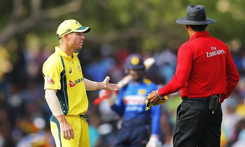 Australia's standing in captain David Warner, left, chats with umpire Ruchira Palliyaguru during their fourth ODI against Sri Lanka in Dambulla. — AP
