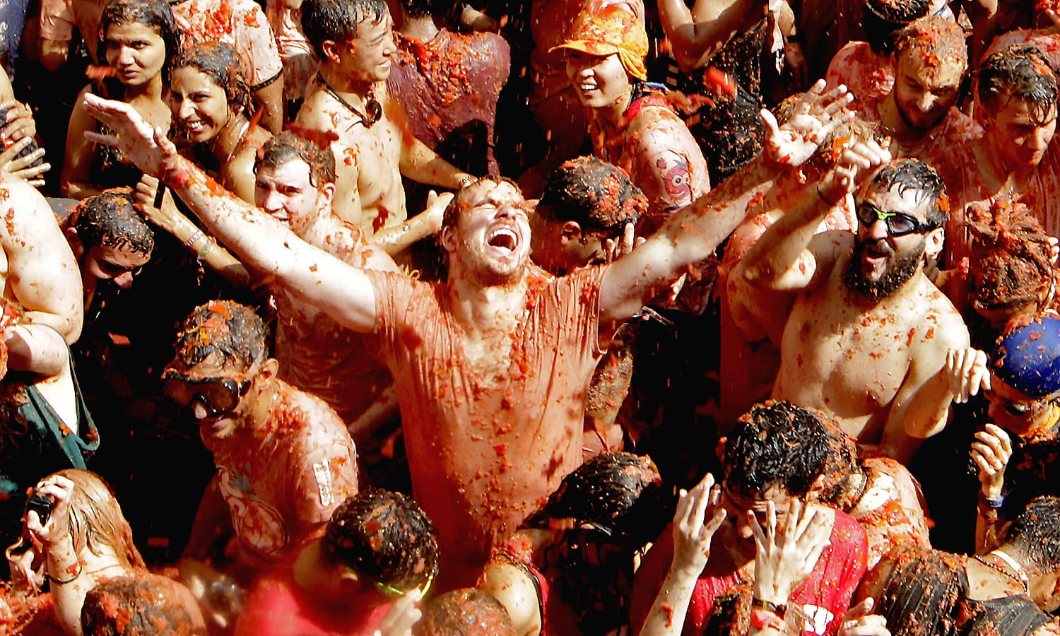 "Revelers enjoy as they throw tomatoes at each other, during the annual ""Tomatina"", tomato fight fiesta, in the village of Bunol, Spain. — AP"