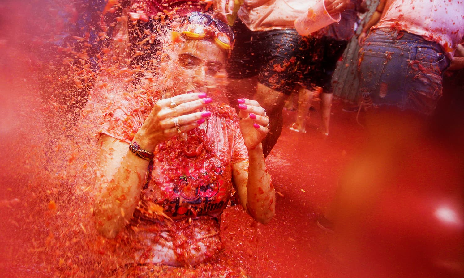 A reveller is covered with tomato pulp. — Reuters
