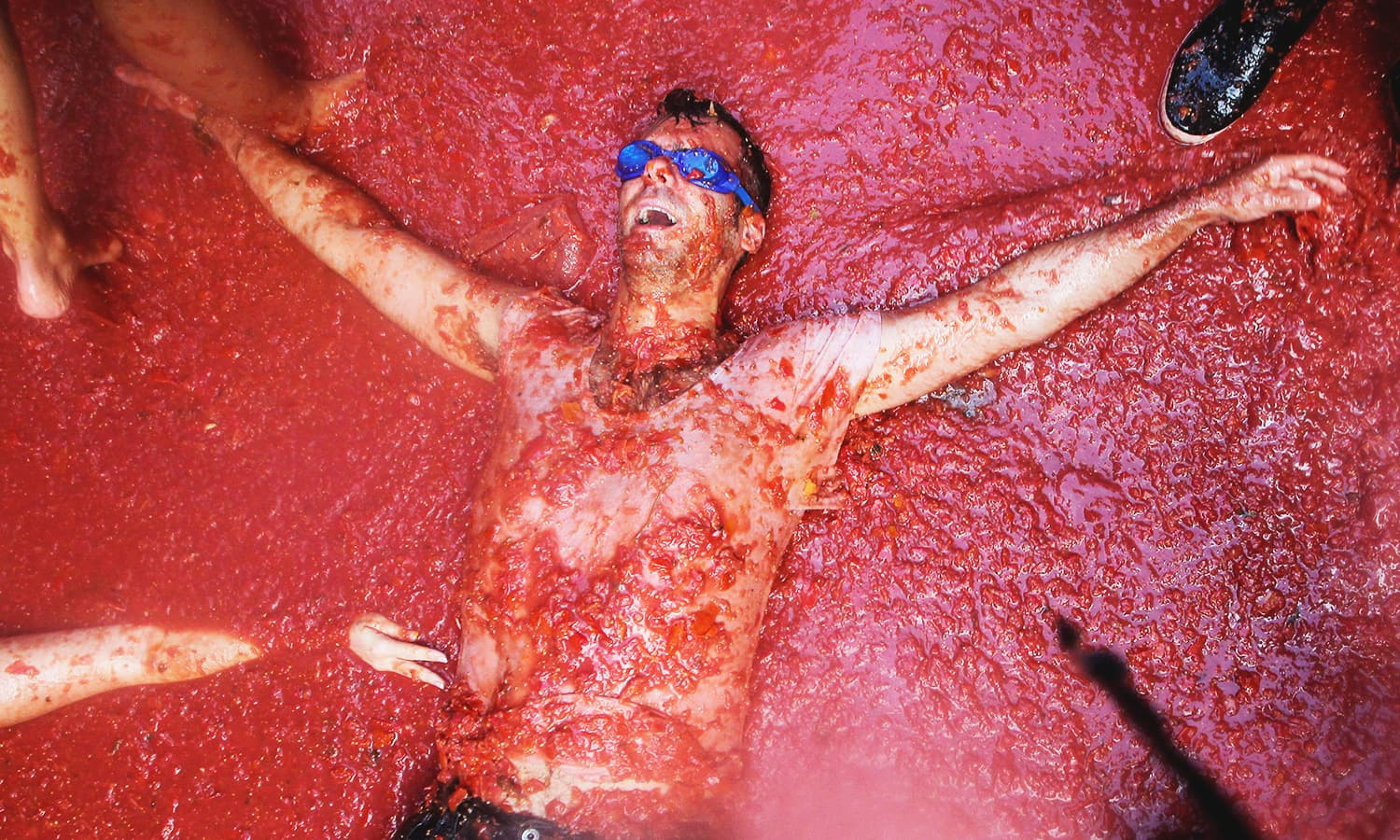 A participant at Tomatina lies in tomato pulp. — Reuters