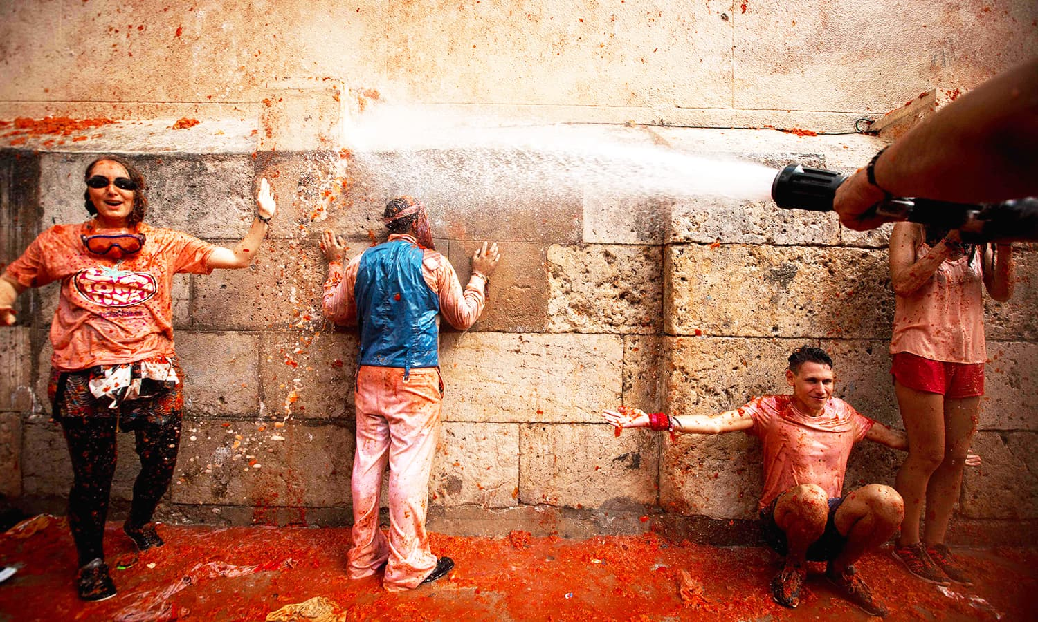 Revellers covered in tomato pulp are hosed down. — AFP