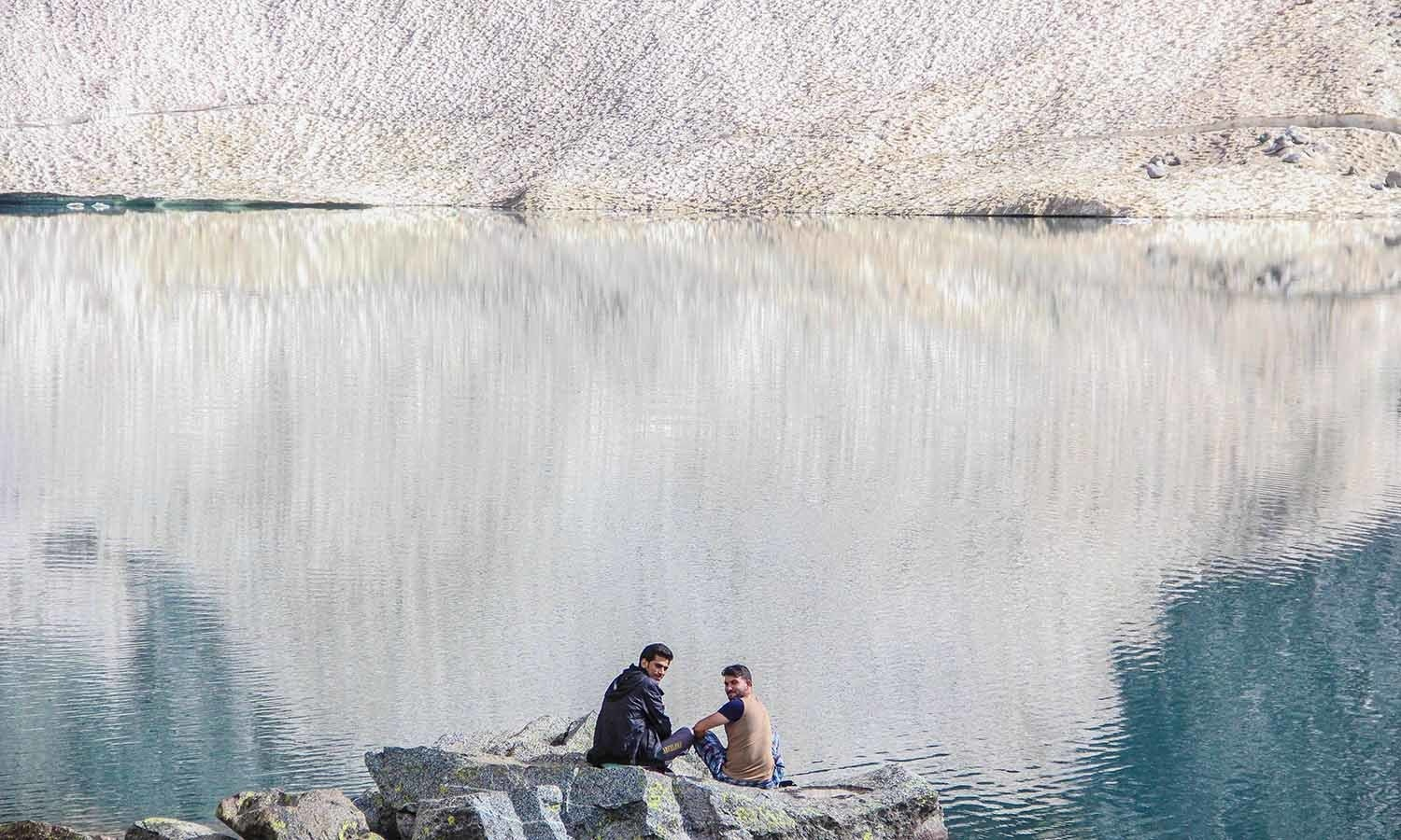 The hard trek is worth the views at the glacial lake.  Trekkers rest at the edge of  Bishigram Lake