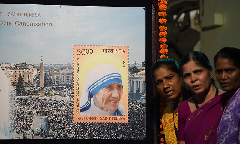 Indian bystanders pose for a picture near a board displaying a commemorative postage stamp of Mother Teresa during its release function in Mumbai on September 4, 2016, ahead of the canonisation of Mother Teresa in Rome. ─ AFP