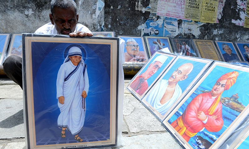 An Indian vendor arranges a photograph of Mother Teresa on a street in Secunderabad, the twin city of Hyderabad on September 4, 2016, ahead of the canonisation of Mother Teresa in Rome. ─ AFP