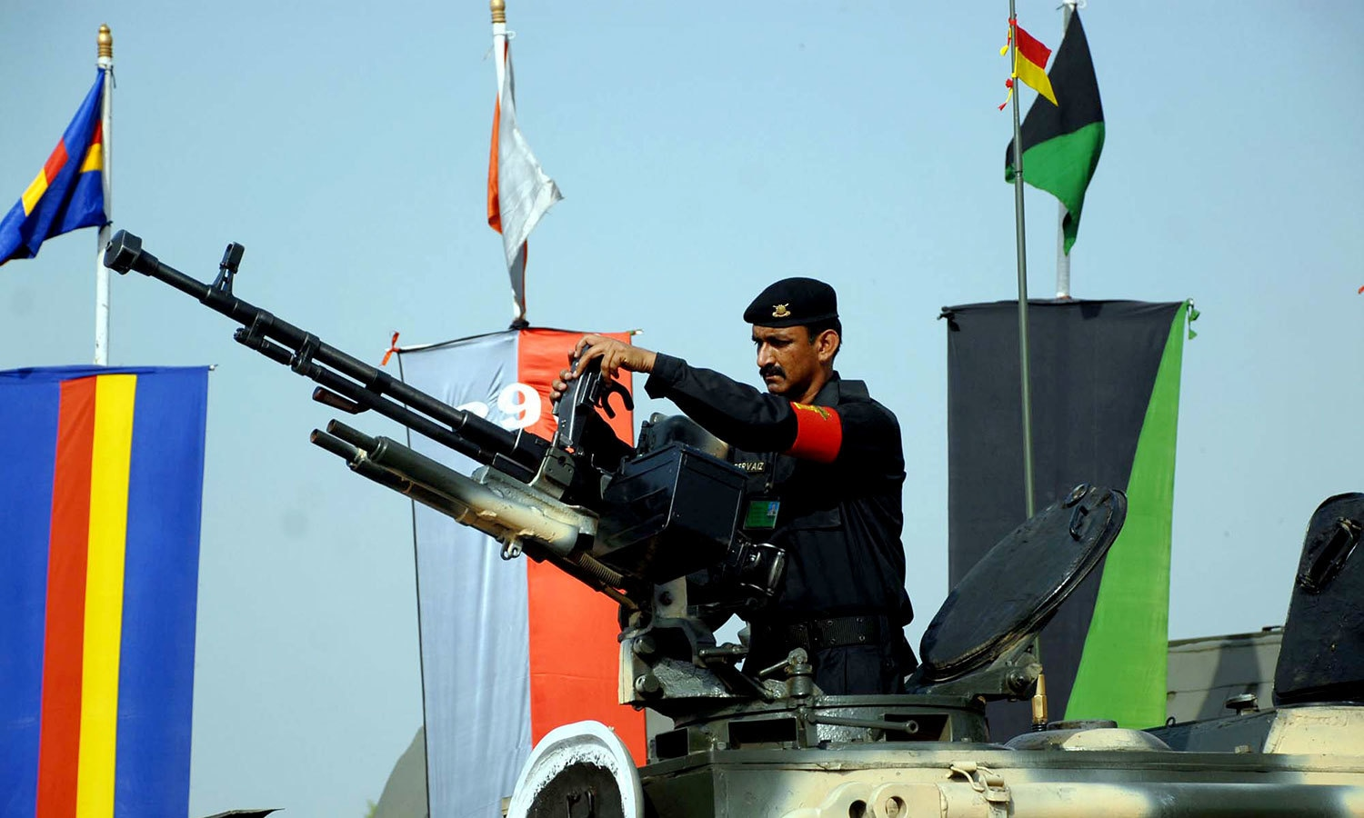 An Army personnel mans a tank's anti-aircraft machine gun. — APP